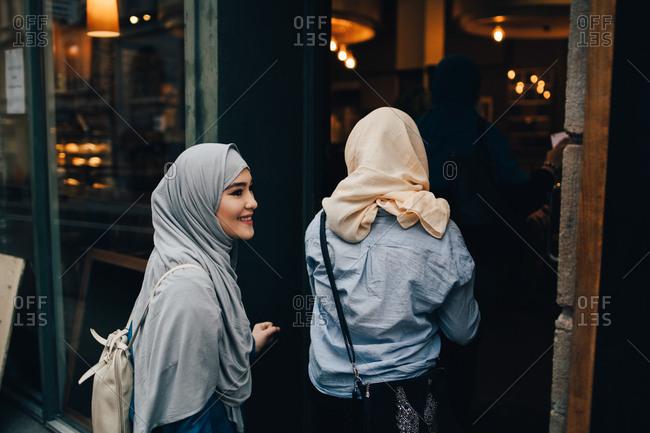 Rear view of young women entering doorway