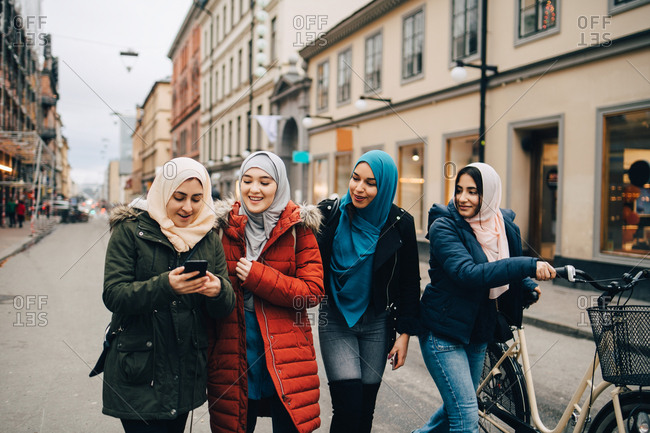 Multi-ethnic Muslim friends walking with bicycle and mobile phone on street in city