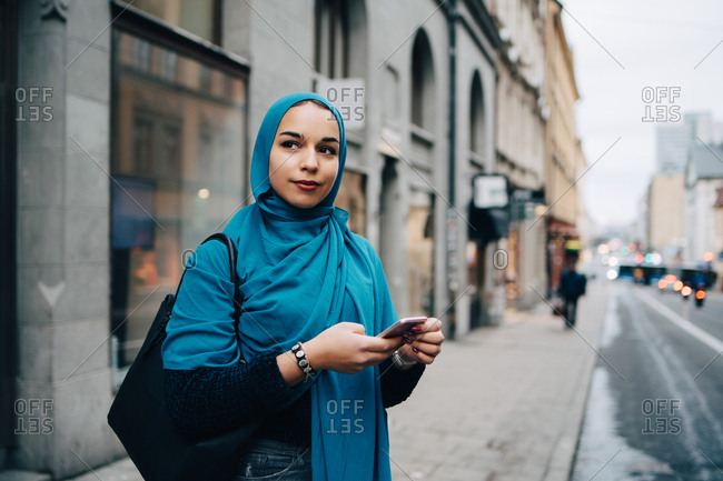 Confident young Muslim woman holding smart phone standing on sidewalk in city