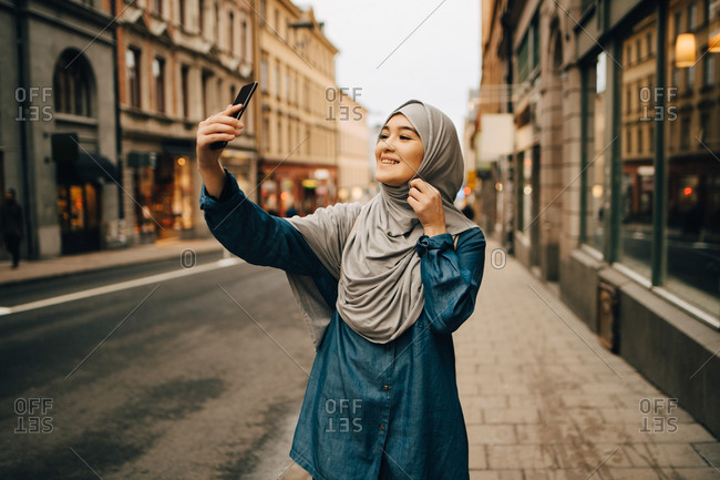 Happy young Muslim woman taking selfie standing on sidewalk in city
