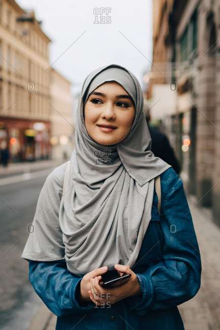 Young Muslim woman wearing hijab walking with mobile phone on sidewalk in city
