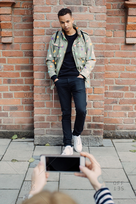 Cropped hands of young woman photographing fashionable man standing with hands in pockets against brick wall