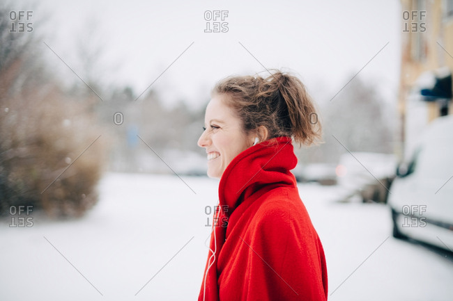 Side view of smiling young woman in red sweater standing on snowy field