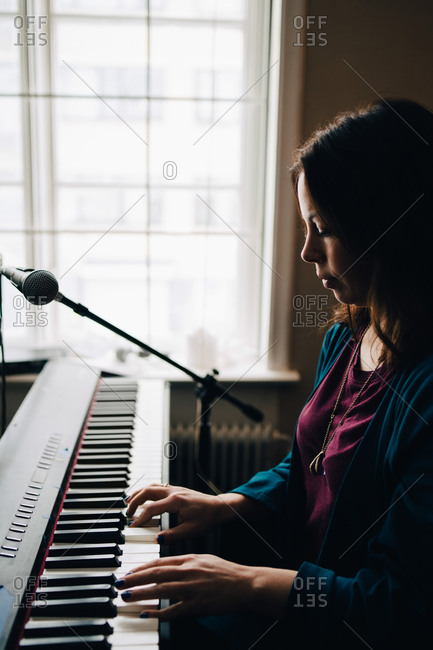 Side view of woman playing piano by window at studio