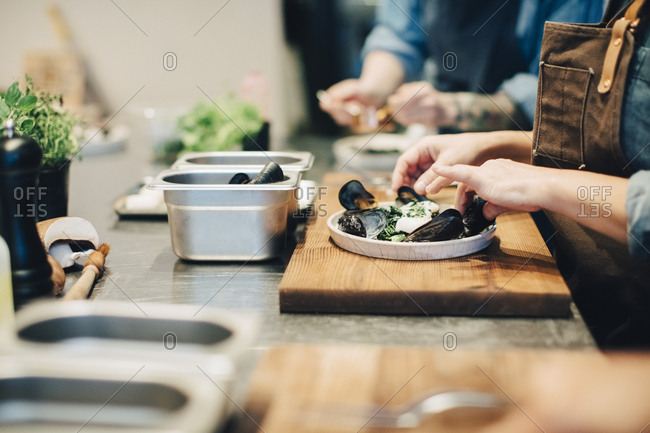 Midsection of female chefs preparing food on counter in restaurant kitchen