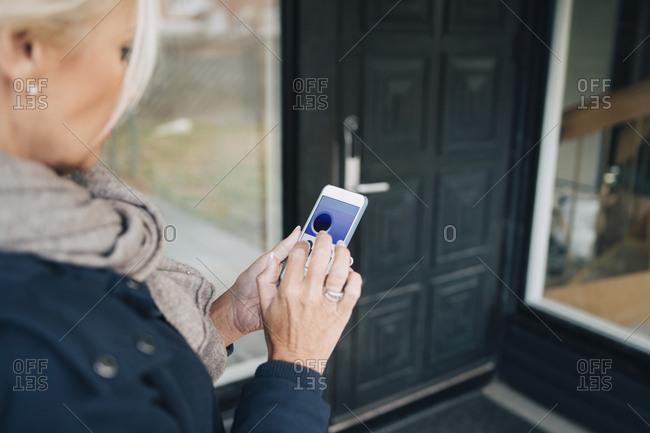 High angle view of woman unlocking house door through smart phone app