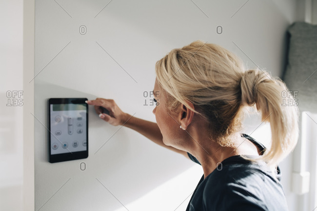 Side view of blond woman adjusting thermostat using digital tablet mounted on white wall at home