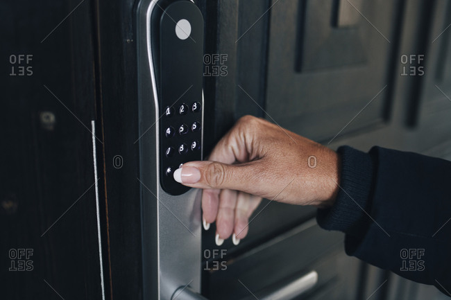 Cropped hand of woman unlocking combination security code on house door