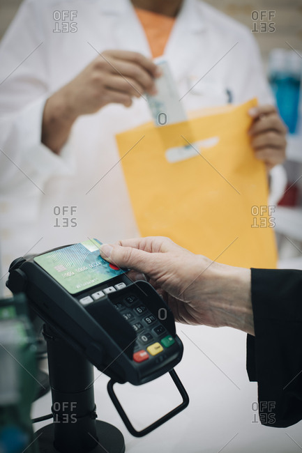 Cropped hand of senior female customer using contactless payment through credit card against pharmacist at checkout in s