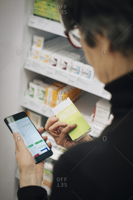 High angle view of senior woman using smart phone for checking medicine at store