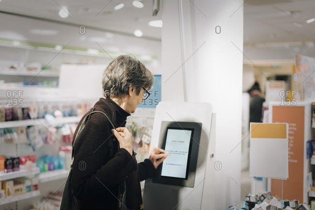 Side view of senior woman using kiosk at pharmacy store