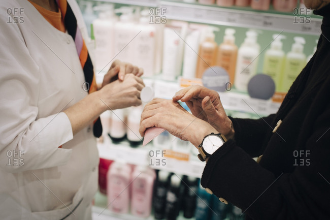 Midsection of senior customer and female owner applying cream on hand at store