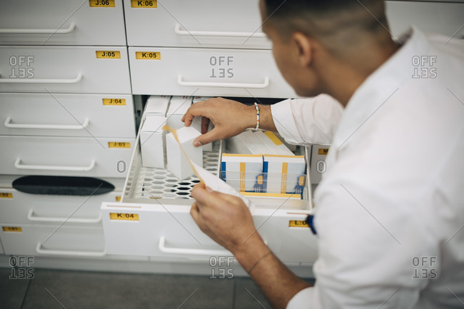 High angle view of male owner holding paper checking medicine from drawer in pharmacy store
