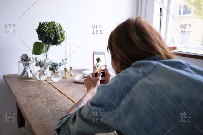 Rear view of blogger photographing flower vases on table through mobile phone