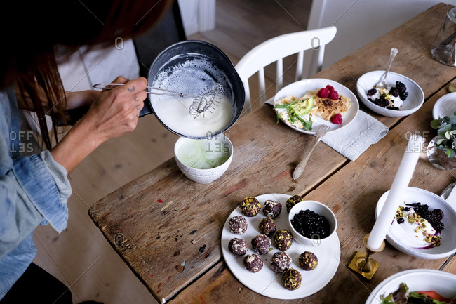 Cropped image of woman preparing matcha tea in bowl at table