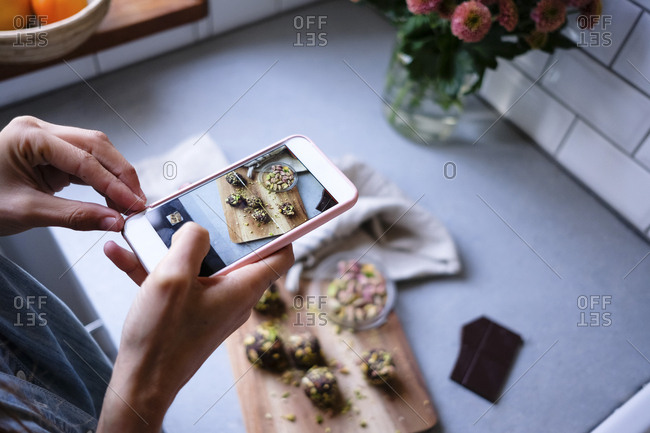 Cropped image of blogger photographing chocolate truffles through smart phone at kitchen counter