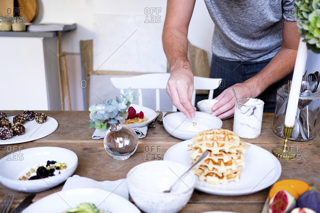 Midsection of man garnishing yogurt in plate at wooden table