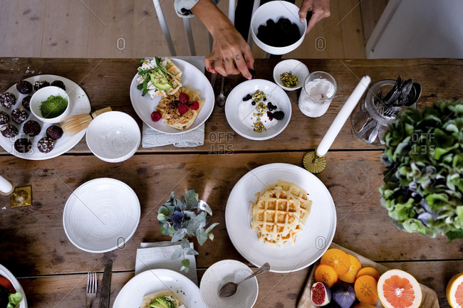 Woman adding blackberries in cream on plate by vase at wooden table