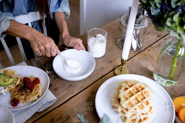 Midsection of woman spreading yogurt on plate at wooden table