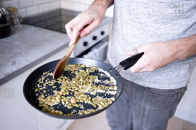 Midsection of man roasting seeds in pan at kitchen