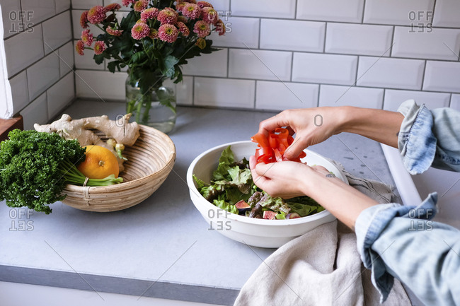 Cropped image of woman making salad at kitchen counter