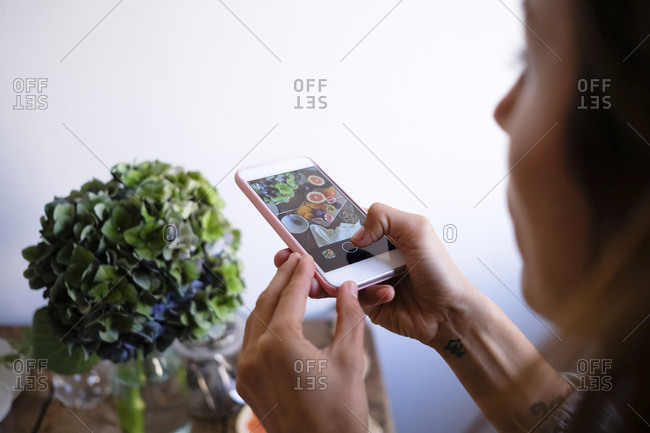 Cropped image of woman photographing food on table by vase at home