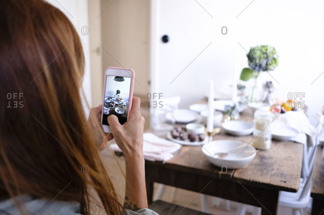 Rear view of woman photographing plates and food on table by wall at home