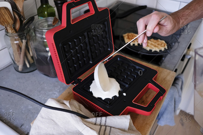Cropped image of man pouring batter on waffle iron at kitchen counter