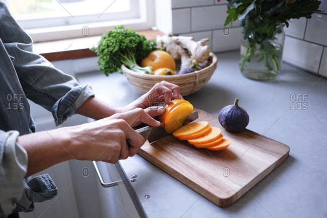 Midsection of woman slicing persimmon on cutting board at kitchen counter