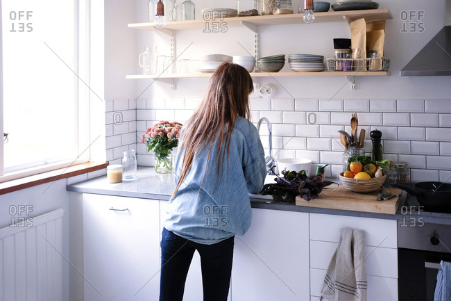 Rear view of woman cooking by window in kitchen