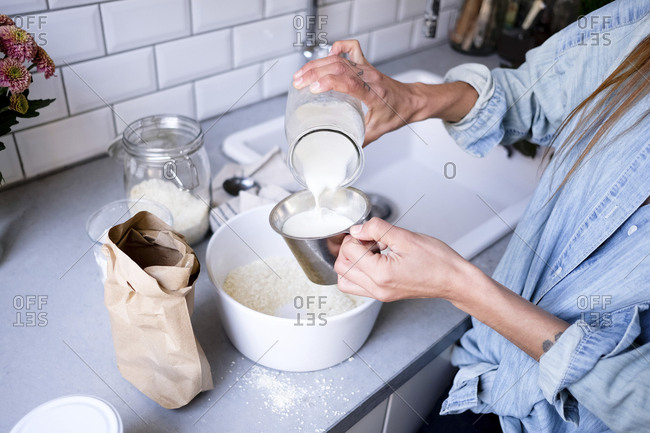 Midsection of woman pouring ingredient in bowl at kitchen counter