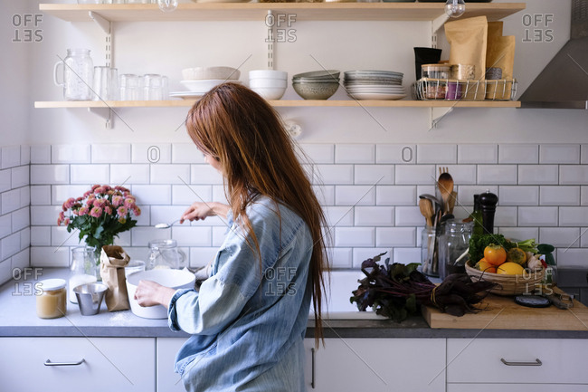 Woman cooking food by kitchen counter at home