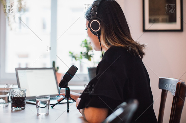 Side view of female podcaster wearing headphones sitting at table with microphone at home