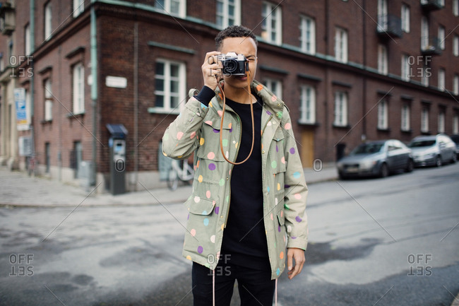 Young male photographer photographing through camera standing on street against building in city