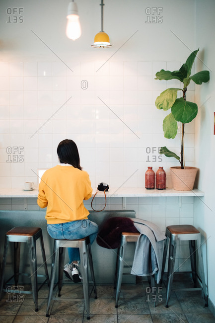 Full length rear view of female blogger sitting on stool at cafe