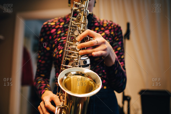 Midsection of woman playing saxophone while practicing at studio