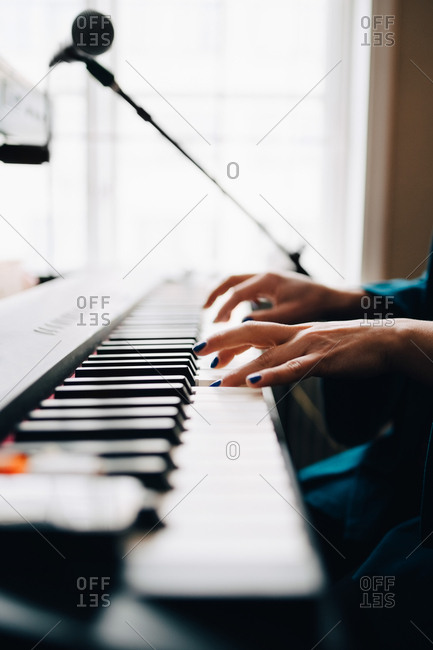 Cropped image of woman playing piano by window at studio