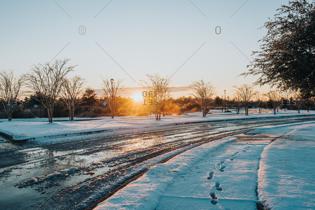 Footprints in snowy sidewalk next to slushy road at sunset