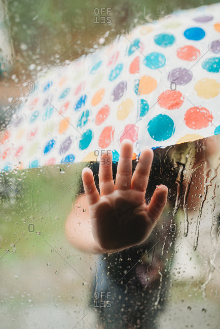Little child holding umbrella standing outside in rain pressing hand against window