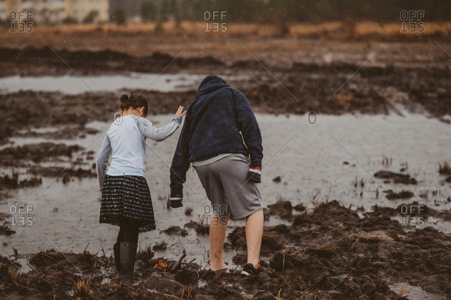 Rearview of boy and younger sister checking depth of puddle in field