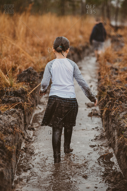 Rearview of young girl following older brother along irrigation canal in the rain
