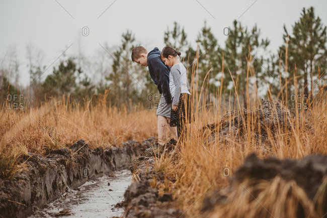 Young girl and older brother standing in the rain looking down at flooded irrigation canal