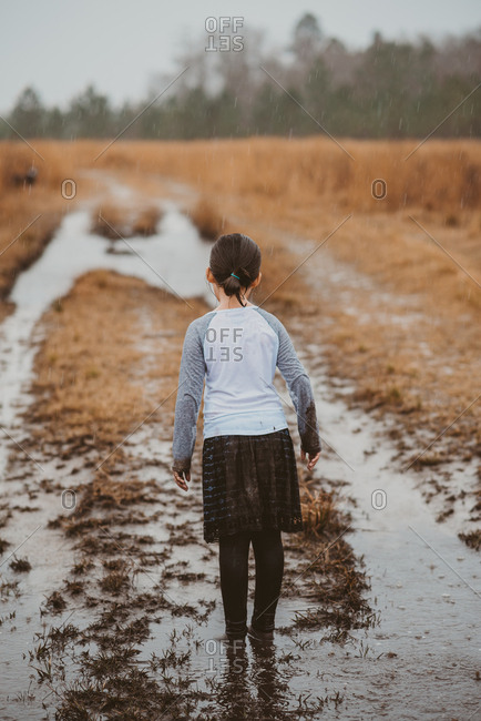 Rearview of young girl standing ankle deep in puddle in field