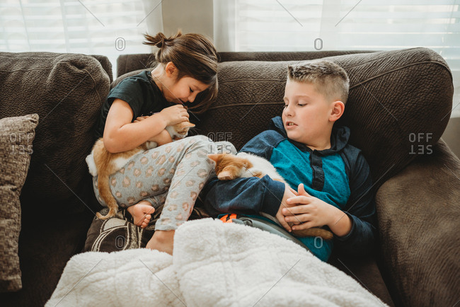 Little girl and brother relaxing on couch hugging their kittens