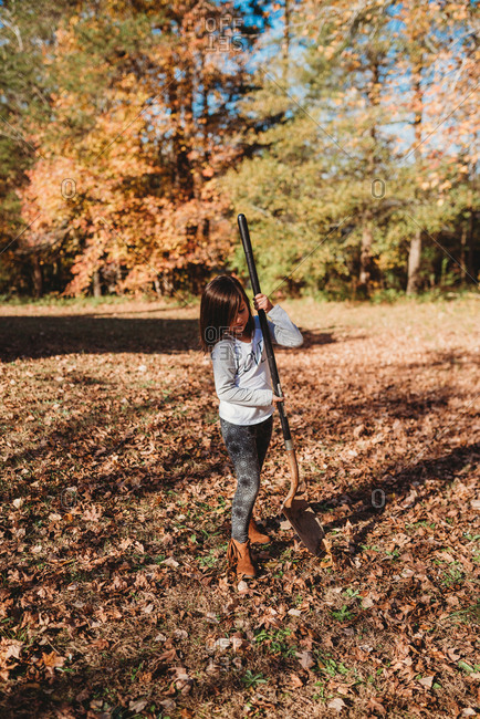 Portrait of young girl holding shovel ready to work in yard
