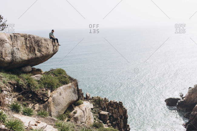 Mid distance view of hiker sitting on cliff while looking at sea