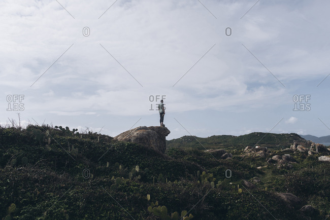 Mid distance view of man standing on rock against cloudy sky