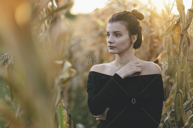 Thoughtful young woman looking away while standing amidst crops on field