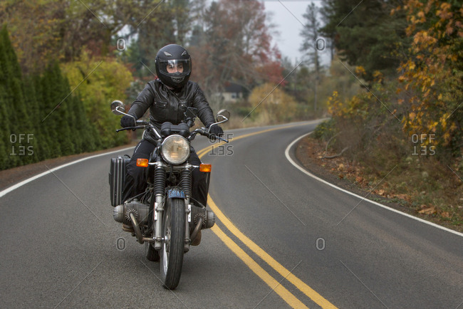 Female biker riding motorcycle on country road