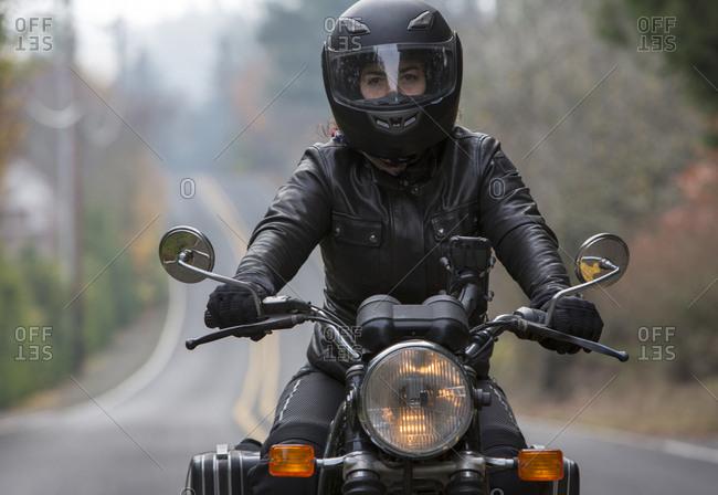 Female biker wearing crash helmet while riding motorcycle on road